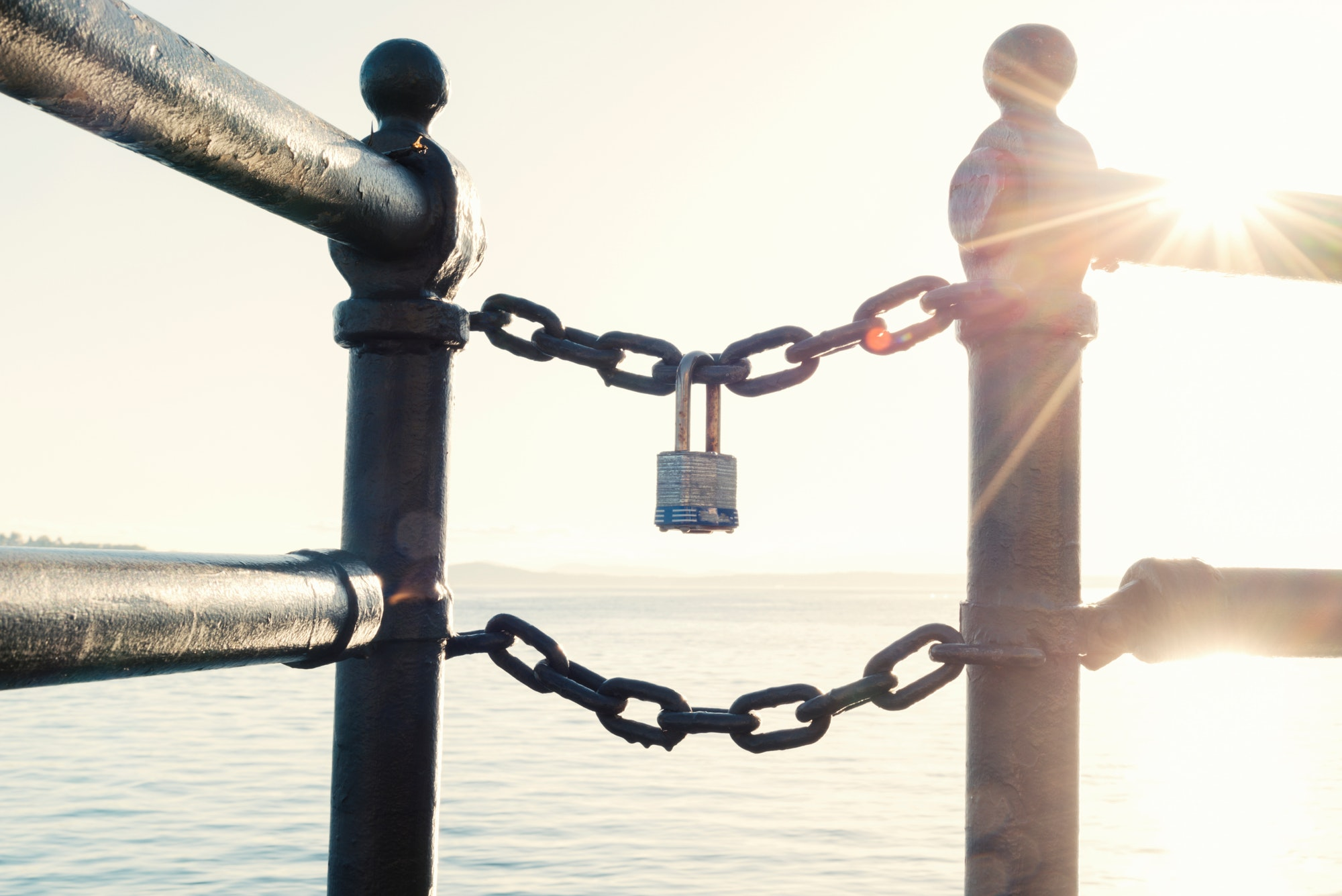 Block chain technology, a lock on a chain at sunset with sunburst.